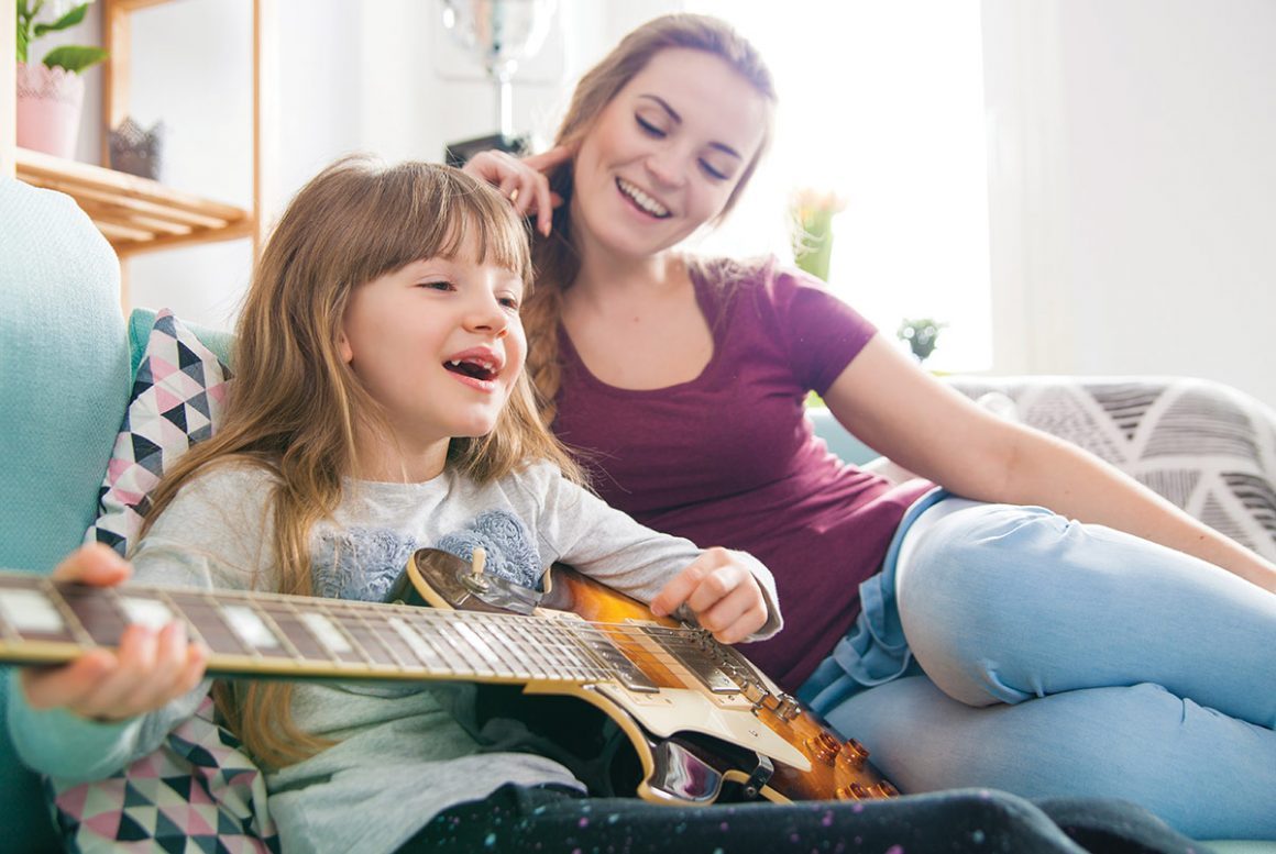 Mom and daughter playing guitar